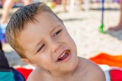 De jongen eet een doughnut op het strand stock foto