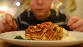 De jongen eet een lasagna in een koffie stock footage