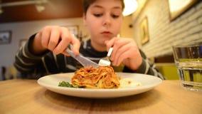 De jongen eet een lasagna in een koffie stock video