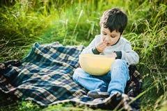 De jongen eet erwten stock fotografie