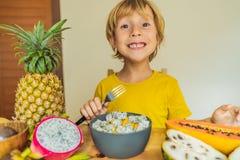 De jongen eet fruit Gezond voedsel voor kinderen Kind die gezonde snack eten Vegetarische voeding voor jonge geitjes Vitaminen vo stock foto's