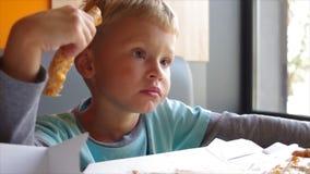 De jongen eet omhoog pizza stock videobeelden