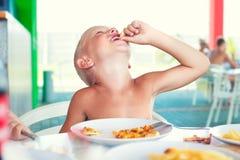 De jongen eet pizza Genoegen van heerlijk voedsel stock afbeelding