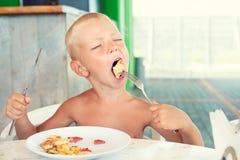 De jongen eet pizza Genoegen van heerlijk voedsel royalty-vrije stock afbeelding