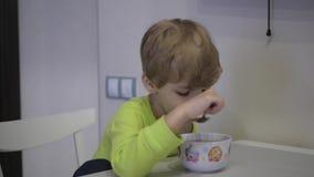 De jongen eet soep bij de lijst stock videobeelden