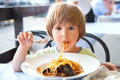 De jongen eet spaghetti Stock Afbeeldingen