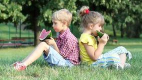 De jongen en het meisje eten watermeloen stock footage
