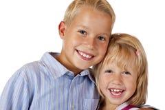 De jongen en het meisje glimlachen gelukkig in camera stock foto
