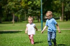 De jongen en het meisje hebben pret en het lopen in park stock foto's