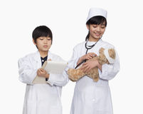De jongen en het meisje kleedden zich omhoog als artsen die de levensteken van de teddybeer controleren Stock Foto