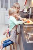 De jongen en het meisje koken iets Stock Fotografie
