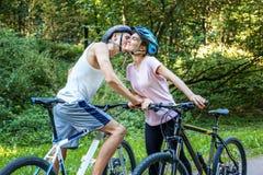 De jongen en het meisje kwamen in het park samen fietsers Het concept van Stock Fotografie