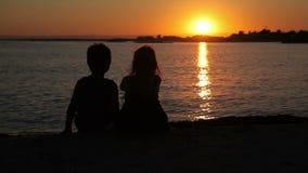 De jongen en het meisje letten op de zonsondergang stock videobeelden