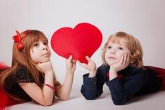 De jongen en het meisje liggen houdend een rood hart royalty-vrije stock foto's