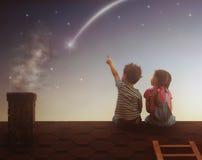 De jongen en het meisje maken een wens Stock Foto's