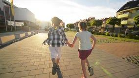 De jongen en het meisje stellen samen het houden van handen op asfalt in werking Zij hebben heel wat pret stock videobeelden