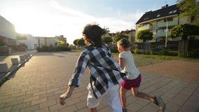 De jongen en het meisje stellen samen het houden van handen op asfalt in werking Zij hebben heel wat pret stock video