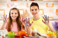De jongen en het meisje tonen het schilderen handen Stock Afbeelding