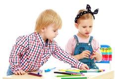 De jongen en het meisje trekken viltpennen Stock Afbeeldingen