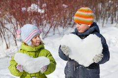 De jongen en het meisje van de tiener houden harten van sneeuw Stock Afbeeldingen