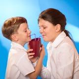 De jongen en het meisje van een kop wordt gedronken die stock foto