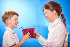De jongen en het meisje van een kop wordt gedronken die stock afbeelding