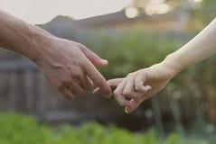 De jongen en het meisje worden gehouden in hand royalty-vrije stock foto's