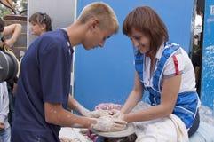 De jongen en het meisje worden gemaakt van kleischotels op het wiel Stock Fotografie