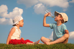 De jongen en het meisje zitten op gras en drank van fles royalty-vrije stock fotografie