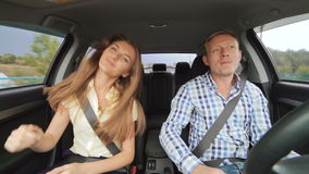 De jongen en meisje die in bedrijfsstijl in de auto in 4K het dansen stock footage