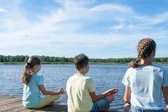 De jongen en twee meisjes zitten door het meer en doen yoga stock afbeelding