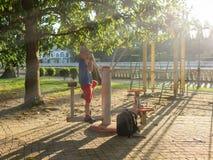 De jongen gaat binnen voor sporten bij de grond van straatsporten in de stralen van zonsondergang stock afbeeldingen
