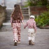 De jongen gaat met zijn mooie zuster voor de gang Royalty-vrije Stock Fotografie