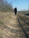 De jongen gaat op een landweg in de afstand royalty-vrije stock afbeelding