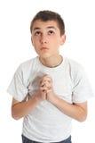 De jongen in gebed kijkt aan hemel voor antwoorden Stock Foto