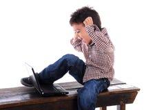 De jongen gebruikt laptop Stock Foto's