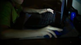 De jongen gebruikt laptop in een donkere ruimte, 4k, close-up van de hand van een kind dat een een computermuis en toetsenbord ge stock footage