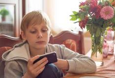 De jongen gebruikt thuis een smartphone stock foto
