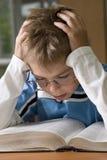 De jongen is geconcentreerd met lezing royalty-vrije stock afbeeldingen