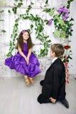 De jongen geeft aan meisje een roze bloem Bekoord weinig Royalty-vrije Stock Afbeeldingen
