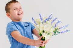 De jongen geeft bloemen Royalty-vrije Stock Foto's