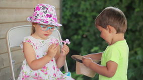 De jongen geeft een meisje bloeit stock videobeelden