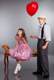 De jongen geeft een rode ballon aan het meisje Stock Afbeelding
