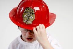 De jongen is gekleed als brandweerman royalty-vrije stock afbeelding