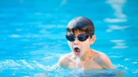 De jongen geniet van zwemmend in de pool Royalty-vrije Stock Foto's