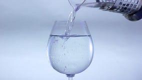 De jongen giet water in een glas stock videobeelden