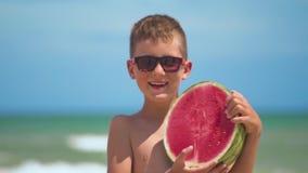 De jongen in glazen houdt een heldere watermeloen op de achtergrond van het overzees stock videobeelden