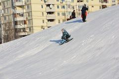 De jongen glijdt gelukkig onderaan een sneeuwheuvel op een slee Stock Afbeeldingen