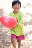 De jongen glimlacht in de hand met een rode ballon trashcan royalty-vrije stock afbeelding