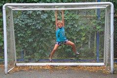 De jongen hangt op kader van doel Stock Foto's
